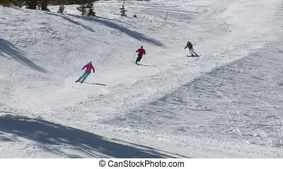 Skiiers glide down path on blue sky day