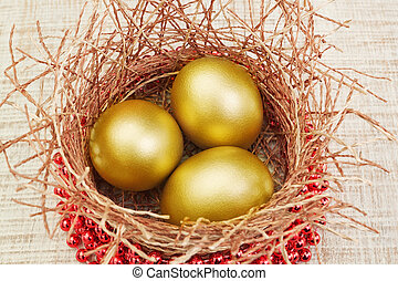Gold eggs in the nest and beads. Concept for Easter.