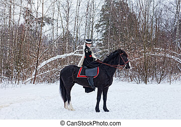 girl in black riding habit sits astride the Oryol trotter