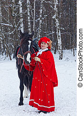 woman keeps a black Oryol trotter in red riding habit