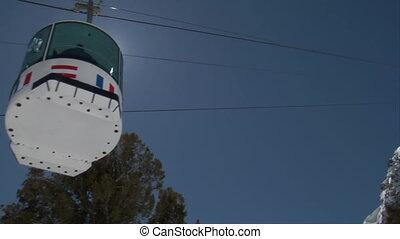 Shot of ski gondola rising into a blue sky
