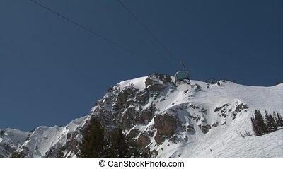 Ski gondola glides downhill against a blue sky