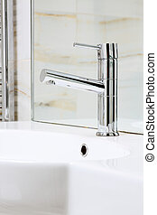 Modern metal faucet on white ceramic wash stand, interior...
