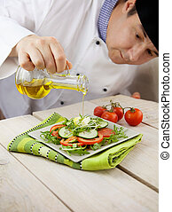 Fresh salad - Food concept. Chef is pouring olive oil over...