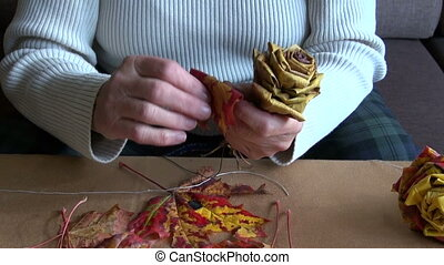make flowers from autumn maple leav - grandmother old hands...