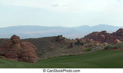 light changes on red rock cliffs with green golf course in...