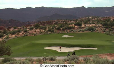 wide shot of golfer hitting ball from sand trap to green