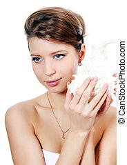 The young beautiful girl with seashell