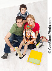 Family with paint preparing to redecorate their home - Happy...