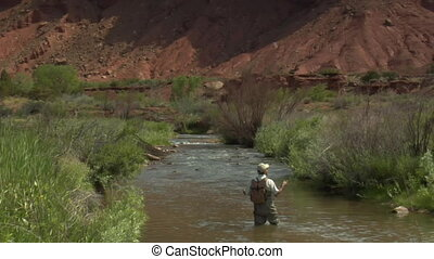 slow motion shot of fly fisherman and red rock cliffs