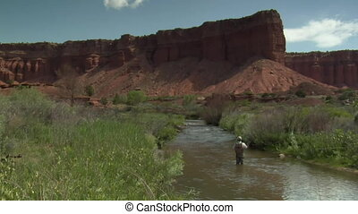 wide shot of fly fisherman and red rock cliffs