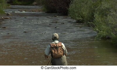 slow motion pull out shot of fly fisherman and red rock...