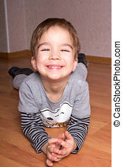 Little smiling boy is lying on a floor at home.