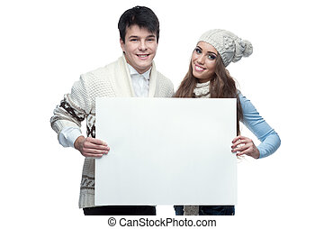 young smiling winter couple holding big sign - young casual...
