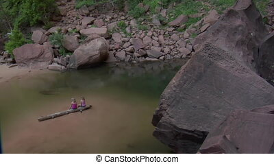 Shot of girls on log in water near boulders