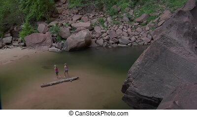 Girls wade through water, pan up to redrock cliff