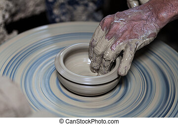 hands on a piece of pottery made of clay on a rotating...