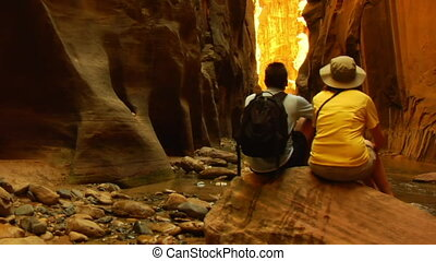 Hiking couple relaxes on rock, admires canyon