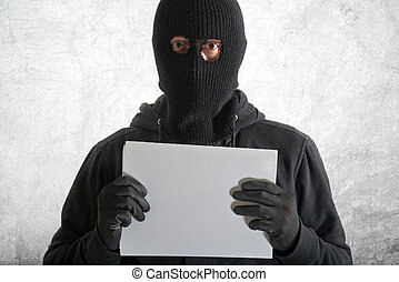 Arrested burglar concept, thief with balaclava caught and...