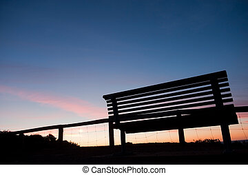 Silhouette of bench at sunset