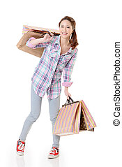 Happy shopping woman of Asian holding bags against white...