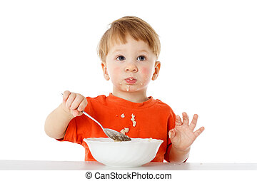 Little boy eating the oatmeal - Little boy learning to feed...