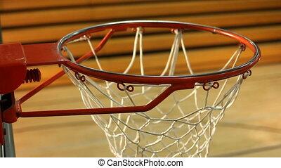Rack focus of basketball hoop in gym