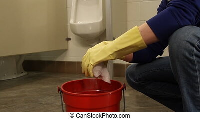 Janitor squeezing out rag in mens bathroom