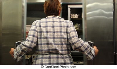 Shot of woman opening industrial refridgerator