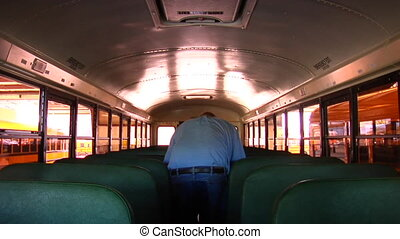 Shot of man walking through empty schoolbus