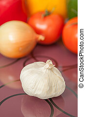 Close up of fresh garlic with fresh vegetables on background