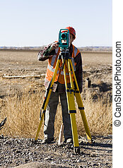 Land surveyors measuring existing railroad bridge in rural...