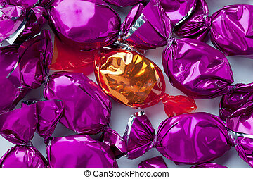 shiny golden candy arranged in between of purple hard...
