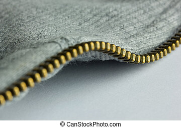 Gold Zip - A close up of a gold zip on a grey item of...