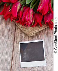 tulips on wooden table with instant foto - fresh red tulips...