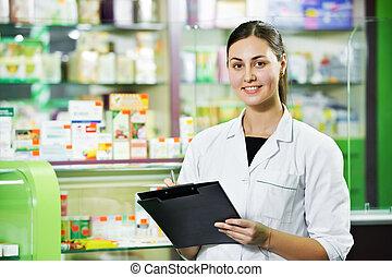 Pharmacy chemist woman in drugstore - pharmacist chemist...