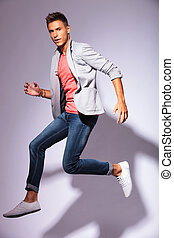 casual young man in the air - portrait of a jumping casual...