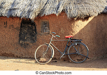 Mud huts and bike in a traditional African village