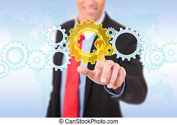 business man pushing a cog button on a word map background