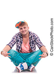 sitting on floor and showing peace - young male urban dancer...