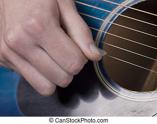 strumming guitar - Human hand strumming a guitar