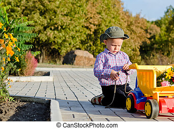 Little boy playing with his truck