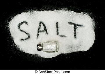 Word Salt on black background written by spilled salt