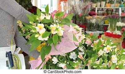 Woman Arranging Flowers In Flower Retail Shop