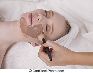 woman having mud face mask - Close up image of woman having...