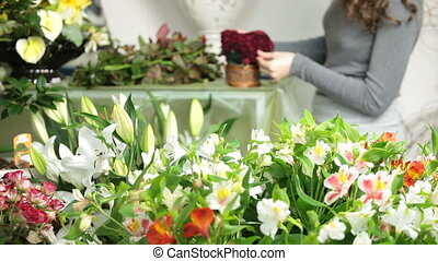 Florist Arranging Bouquet - Large array of flowers in...