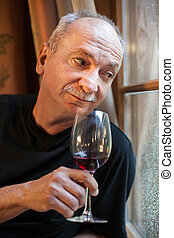 elderly man near the window with a glass of wine - An...