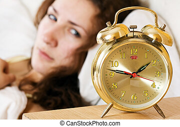 Insomnia - Clock with sleep at night. Woman can not sleep.