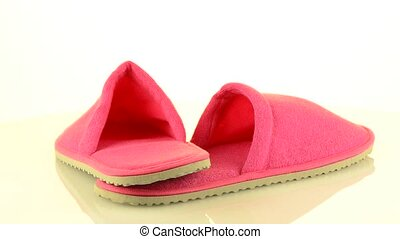 A pair of pink slippers on a white background