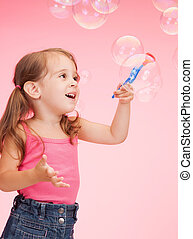 Little girl with soap bubbles - bright picture of beautiful...